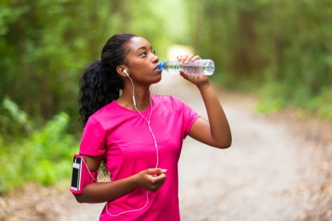African-american-woman-jogger-drinking-water-Fitness-people-and-healthy-lifestyle-805x537
